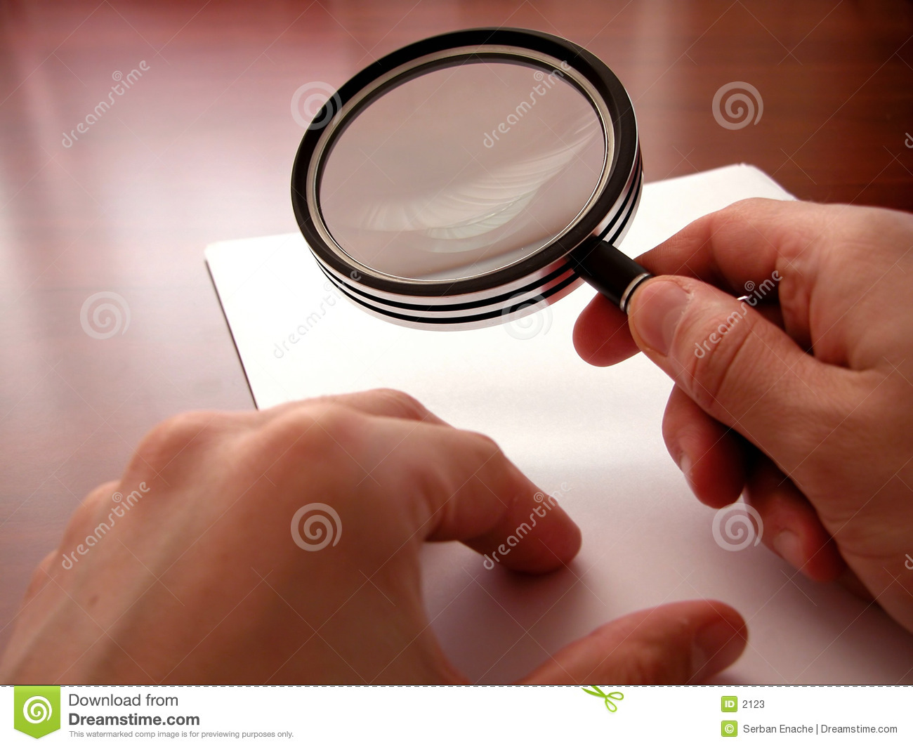 Holding a magnifying lens