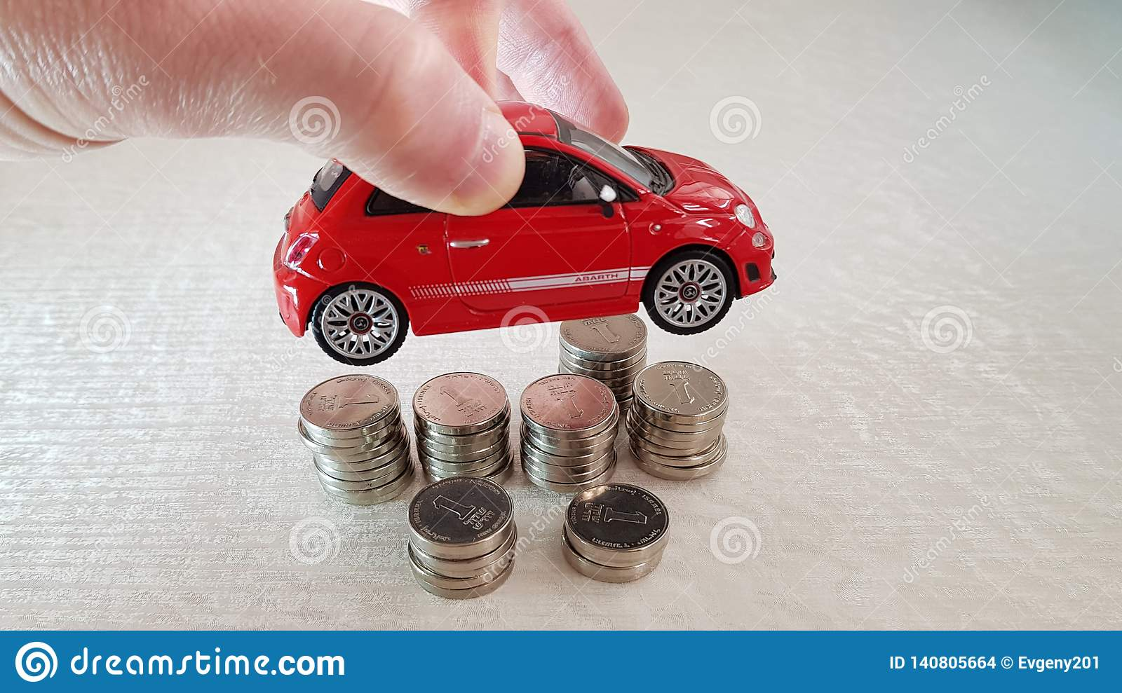 Holds in his fingers small red fiat 500 toy over pile of one Israeli shekel coins