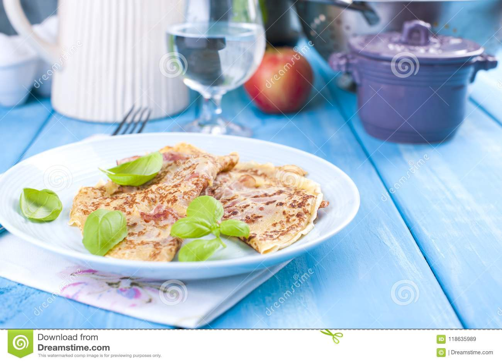 Holenderscy bliny z baleronem dla śniadaniowych Jaskrawych kolorów, błękitny tło Smakowity i caloric szklankę wody Uwalnia przest