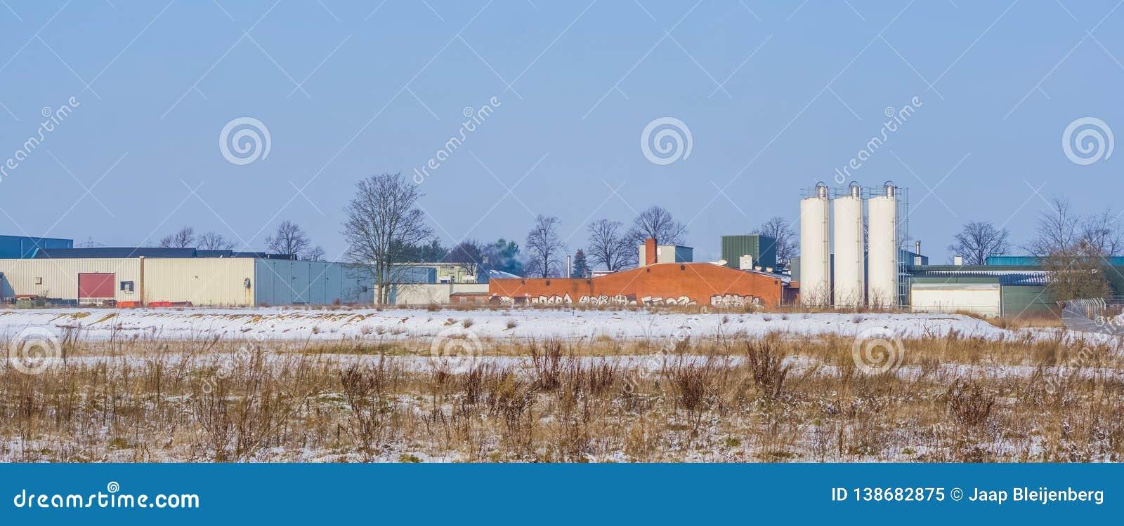Holenderski przemysłu krajobraz z magazynem i niektóre białymi zbiornikami, Majoppeveld przemysłowy teren w mieście Roosendaal