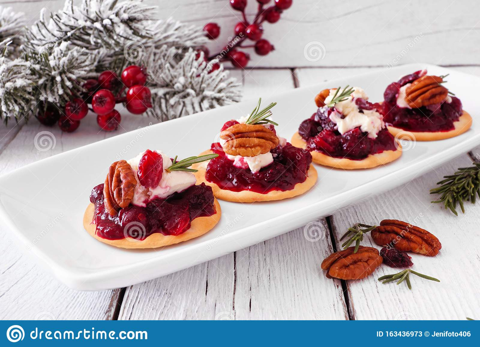 Holiday appetizers with cranberries, goat cheese and pecans on a serving plate, close up against white wood