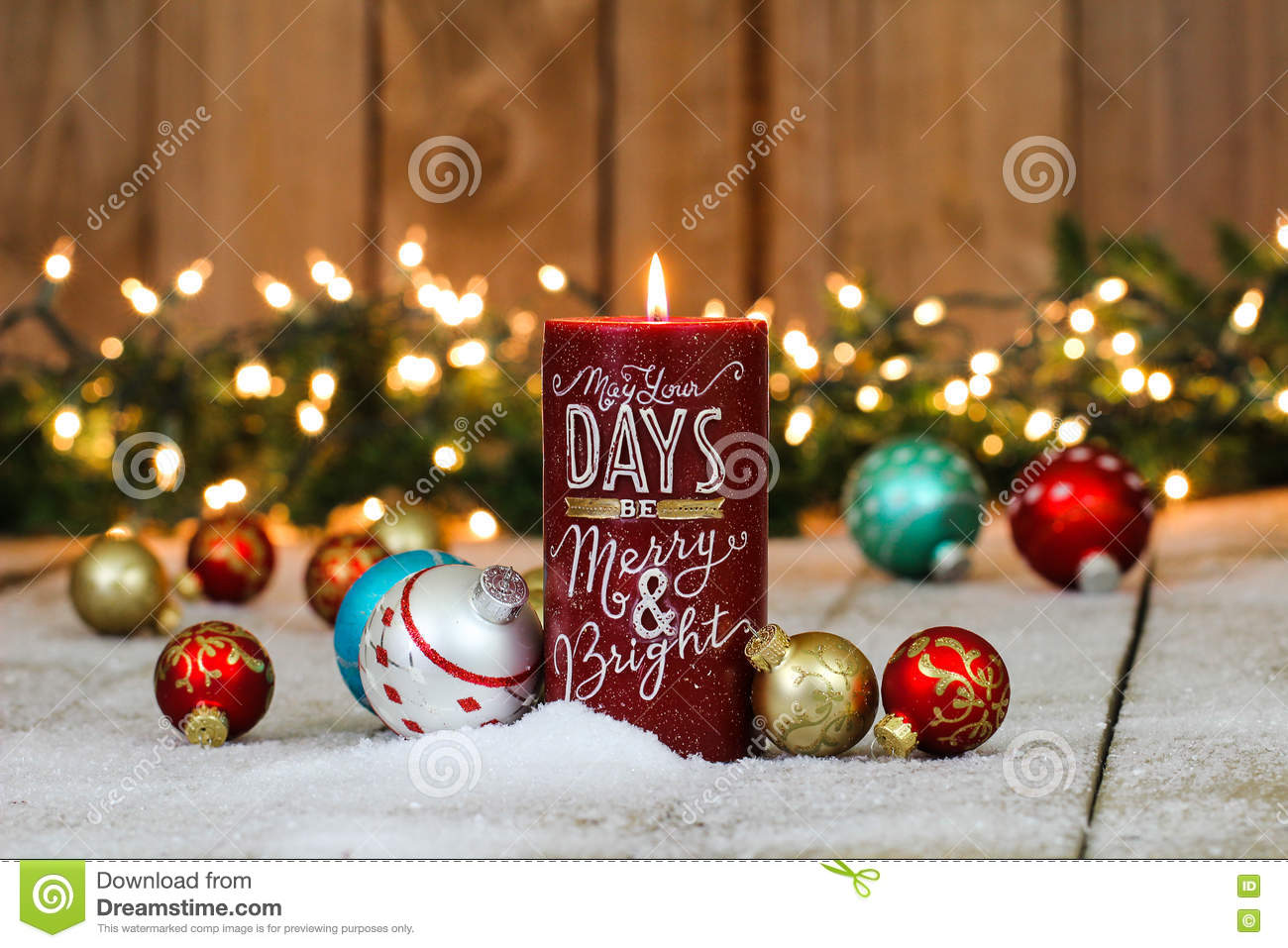 christmas background with red candle colorful ornaments and string of holiday lights and garland border in snow teal blue silver gold red green