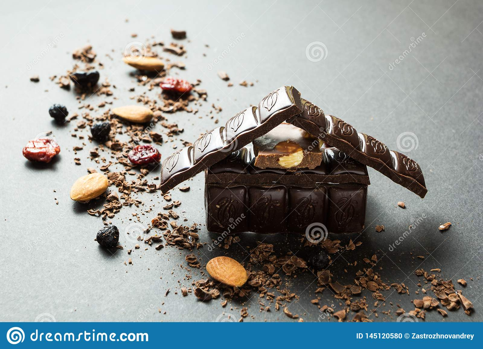 Holiday chocolate house and dried fruits with nuts on a black background