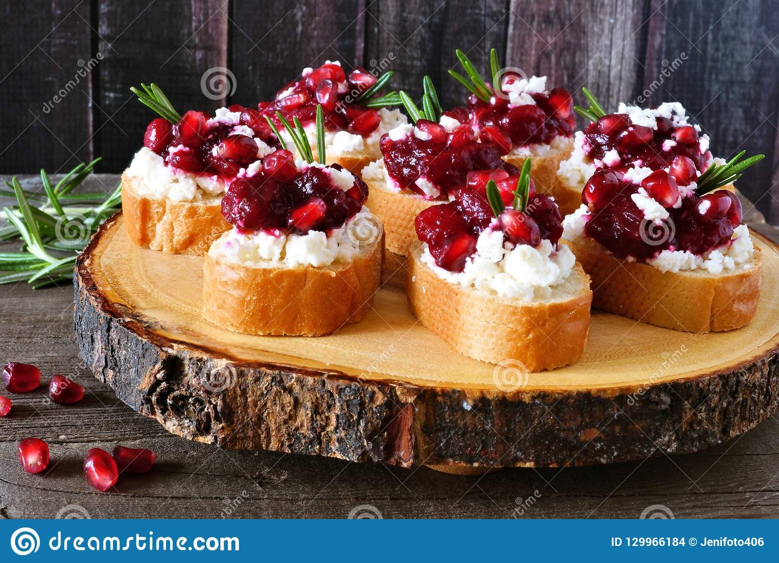 Holiday Crostini Appetizers With Cranberries Pomegranates And Feta On A Wood Log Platter Stock Photo Image Of Holiday Appetizer 129966184