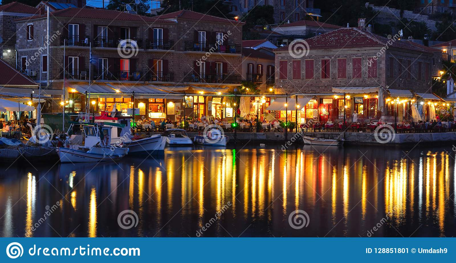 Holiday makers dining in harbor side restaurants Molyvos Greece