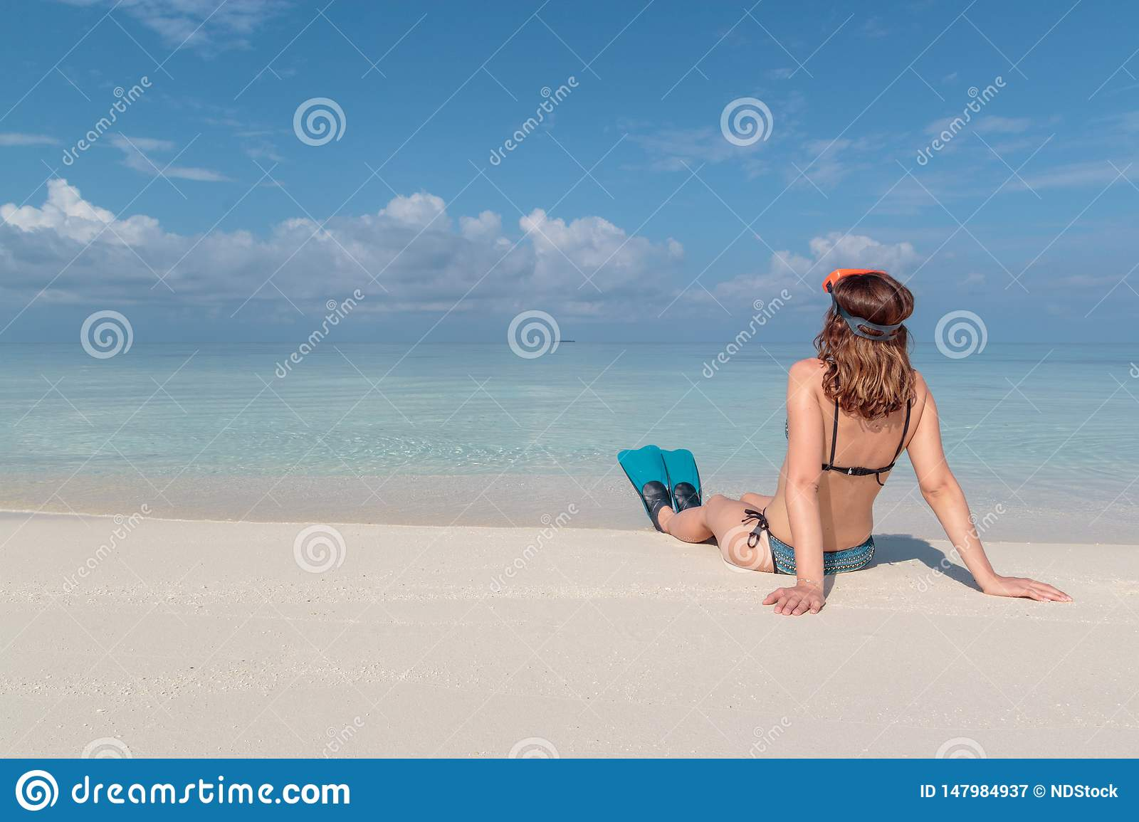 Picture from back of a young woman with flippers and mask seated on a white beach in the Maldives. Crystal clear blue water as