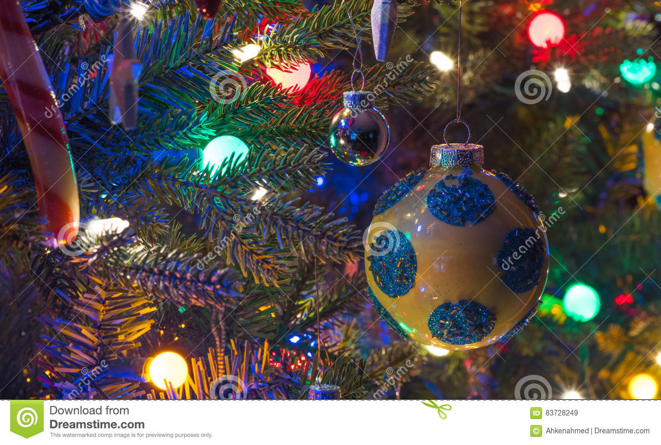 yellow ball with blue spots matte and shiny silver big and small holiday decoration balls hang on a small faux indoor christmas tree bathed in coloured - Big Indoor Christmas Decorations
