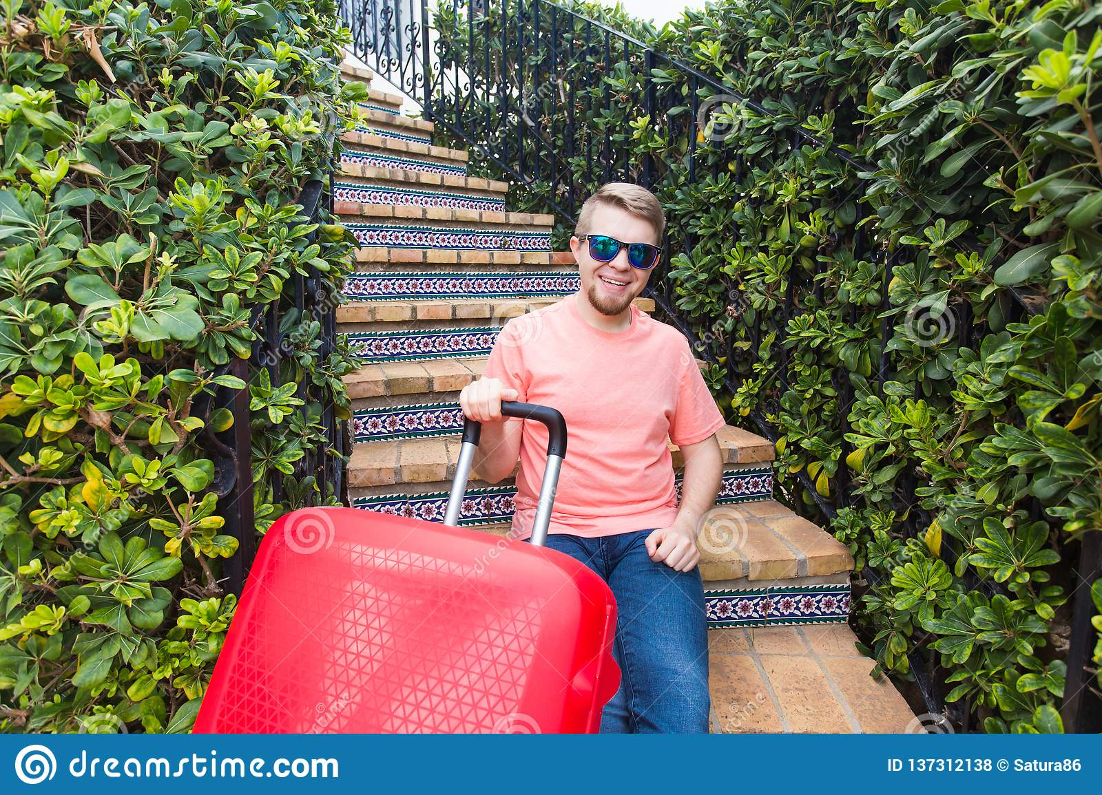 Holiday, travelling and baggage concept - young man with suitcase sitting on stairs