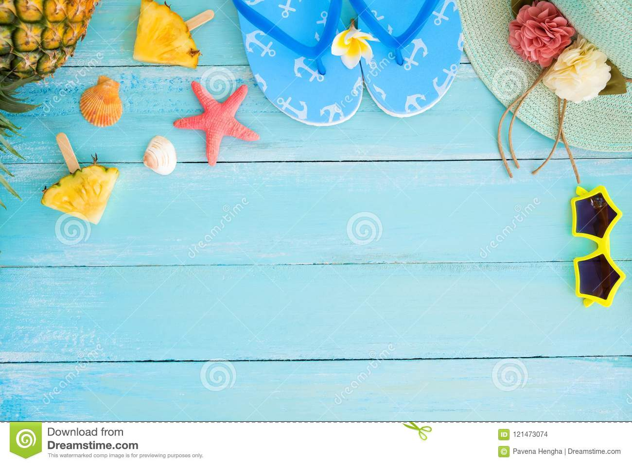 Pineapple slices, shells, starfish, slippers, straw hat and sunglasses on wood plank blue color.