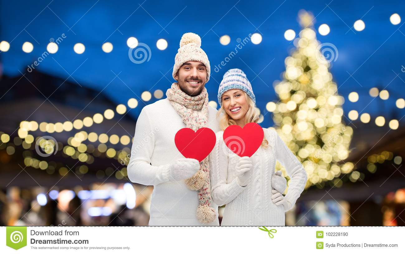 Couple With Red Hearts Over Christmas Tree Lights Stock