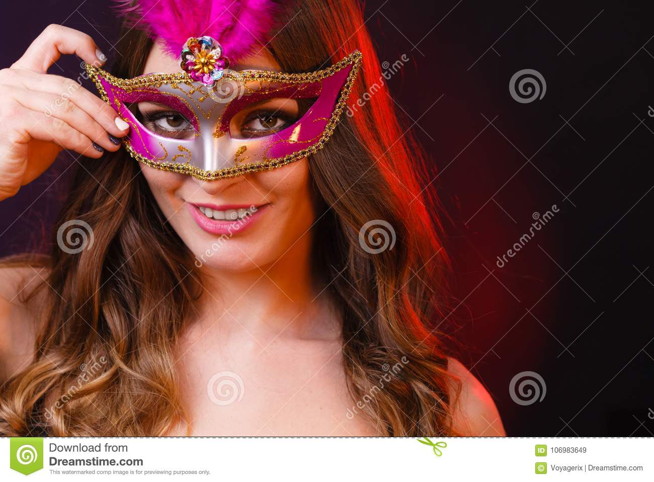 c089b29cdebb Holidays, people and celebration concept. Closeup woman face with carnival  pink feather mask on dark background.