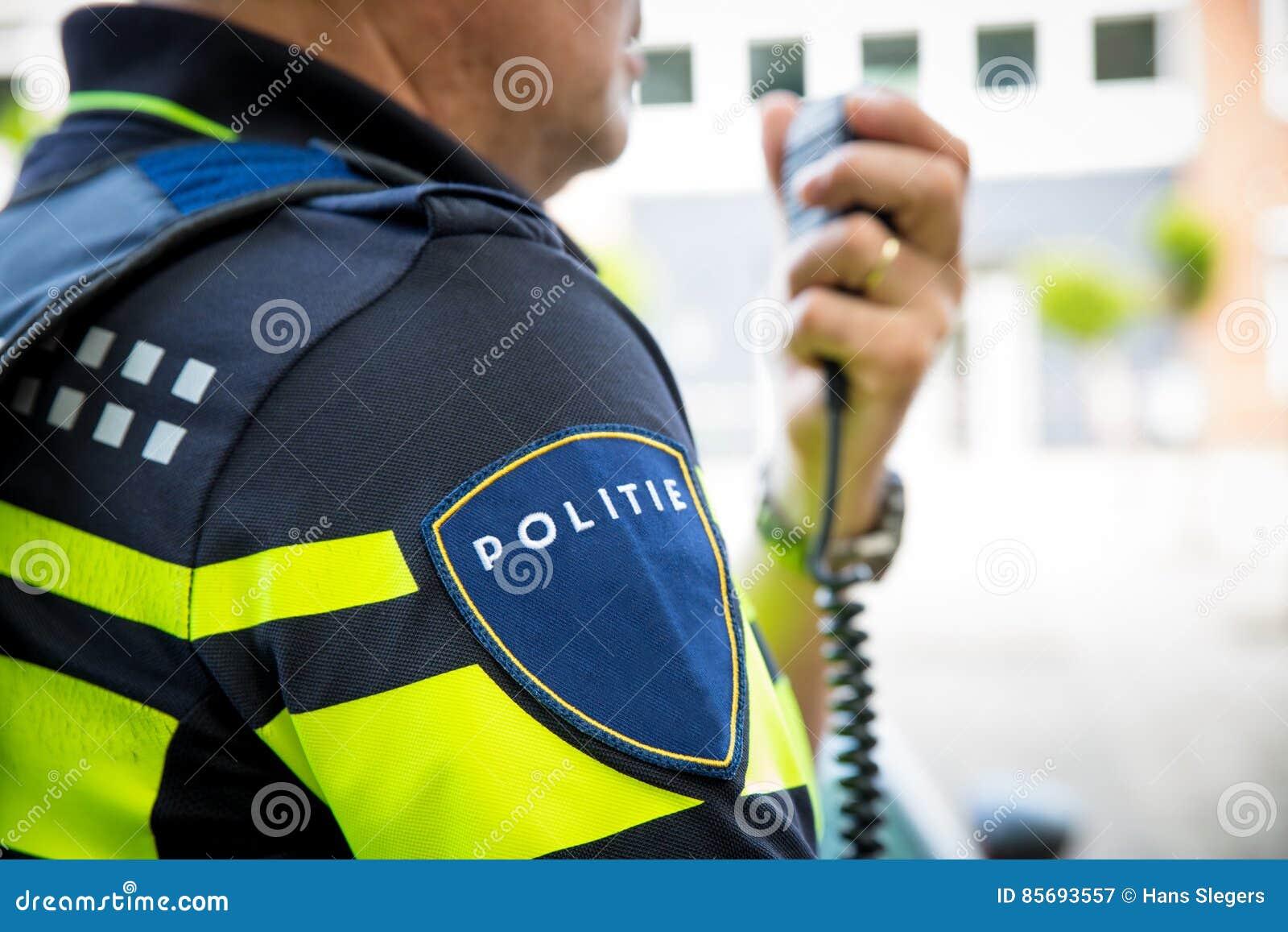 Holländsk polis med radiofokusen på emblem med logo