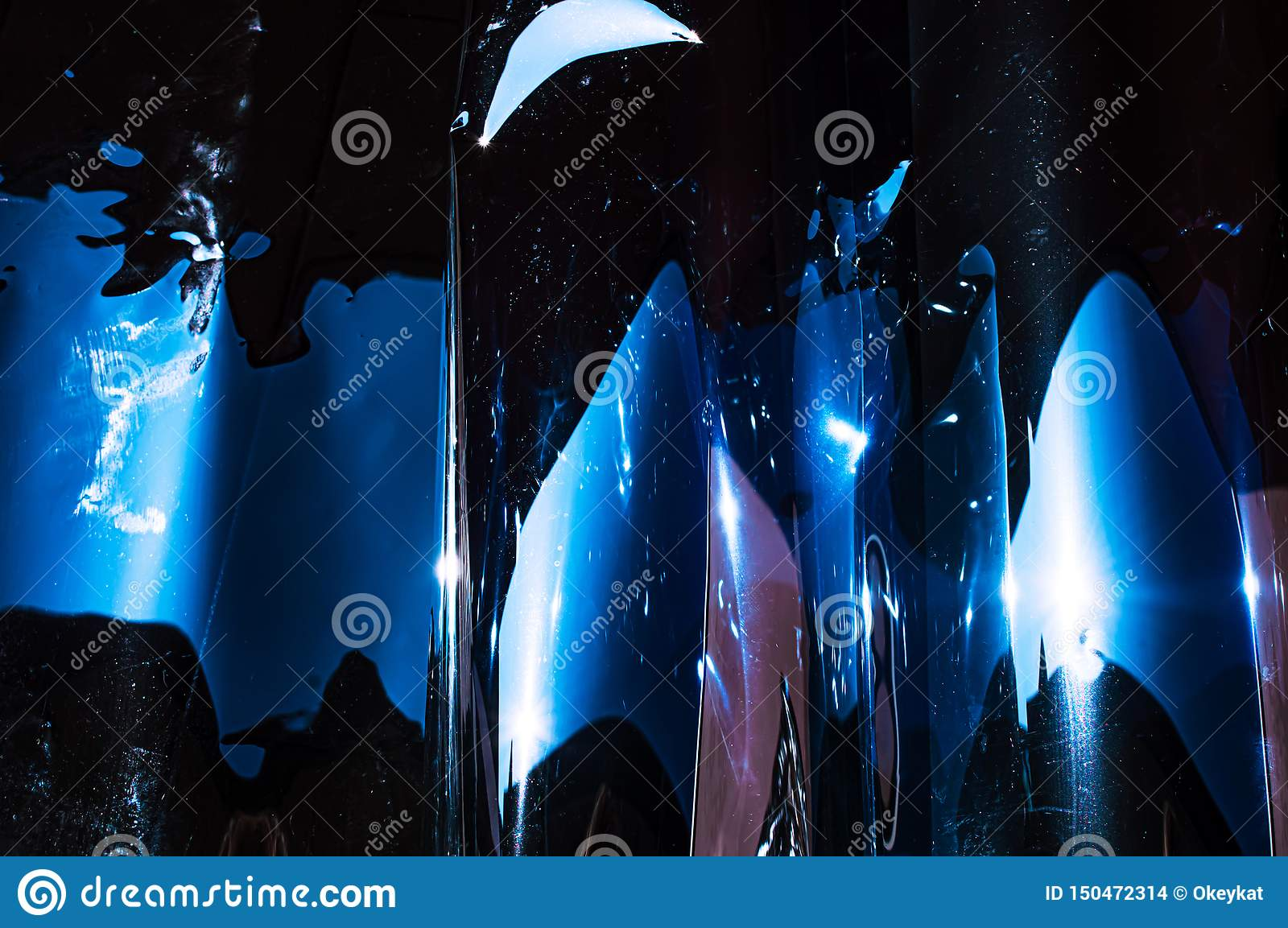 Holographic plastic wrinkled film with contrast sun light reflections. Blue tones with dark black shadows