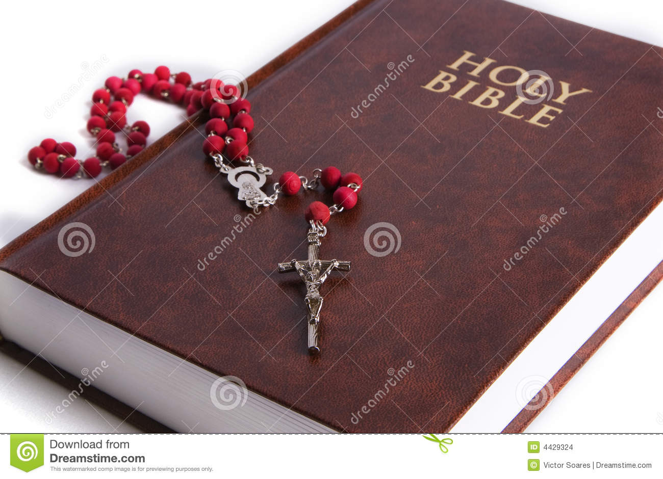 The holy bible displayed with a red rosary on it focus is on the