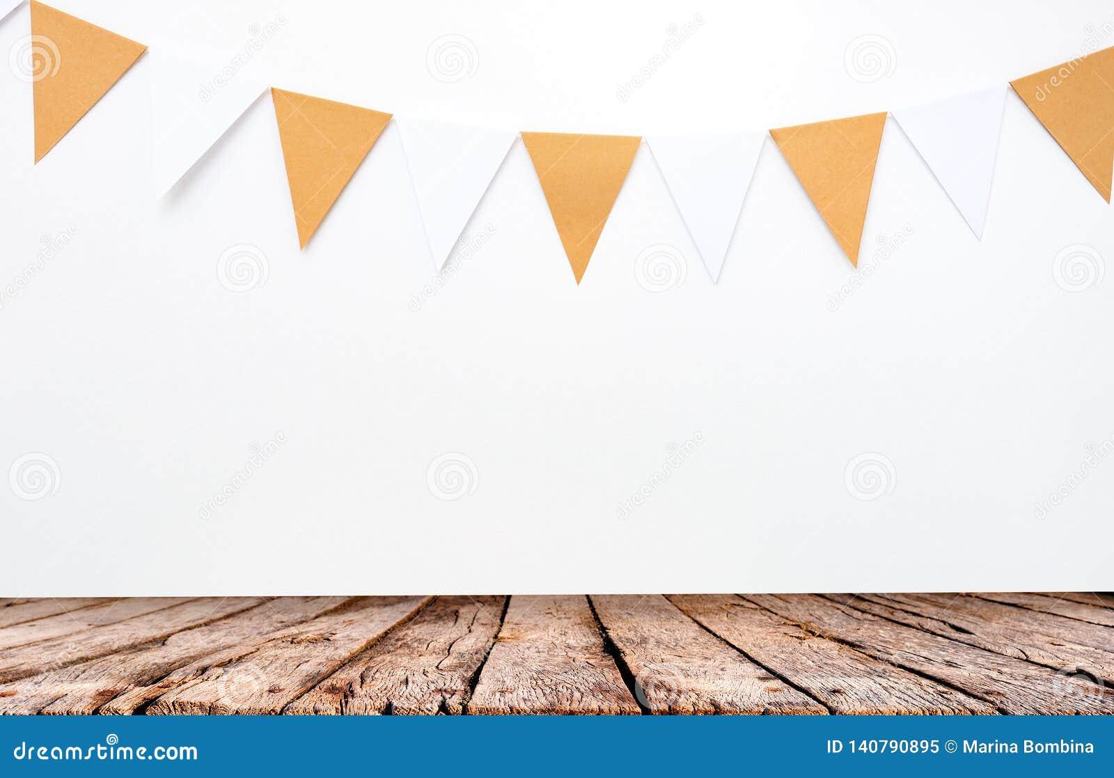 Holztisch und hängende Papierflaggen auf weißem Wandhintergrund, Dekoreinzelteile für Partei, Festival, feiern Ereignis