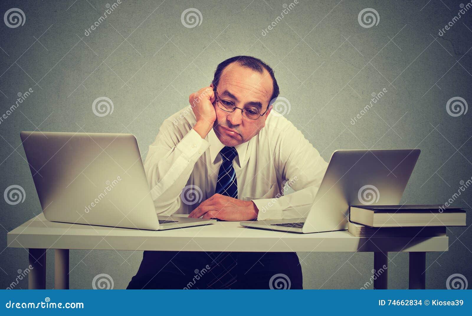 Hombre aburrido que se sienta delante de dos ordenadores portátiles
