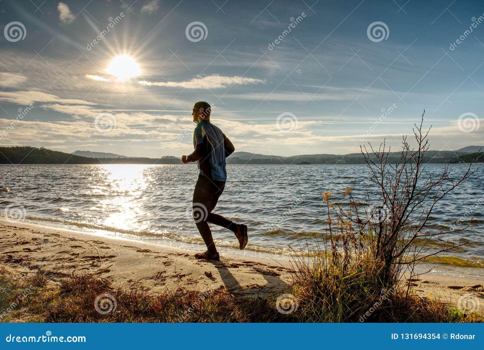Hombre activo que corre en el lago Vacaciones sanas del concepto de la forma de vida de la aventura del viaje, persona atlética