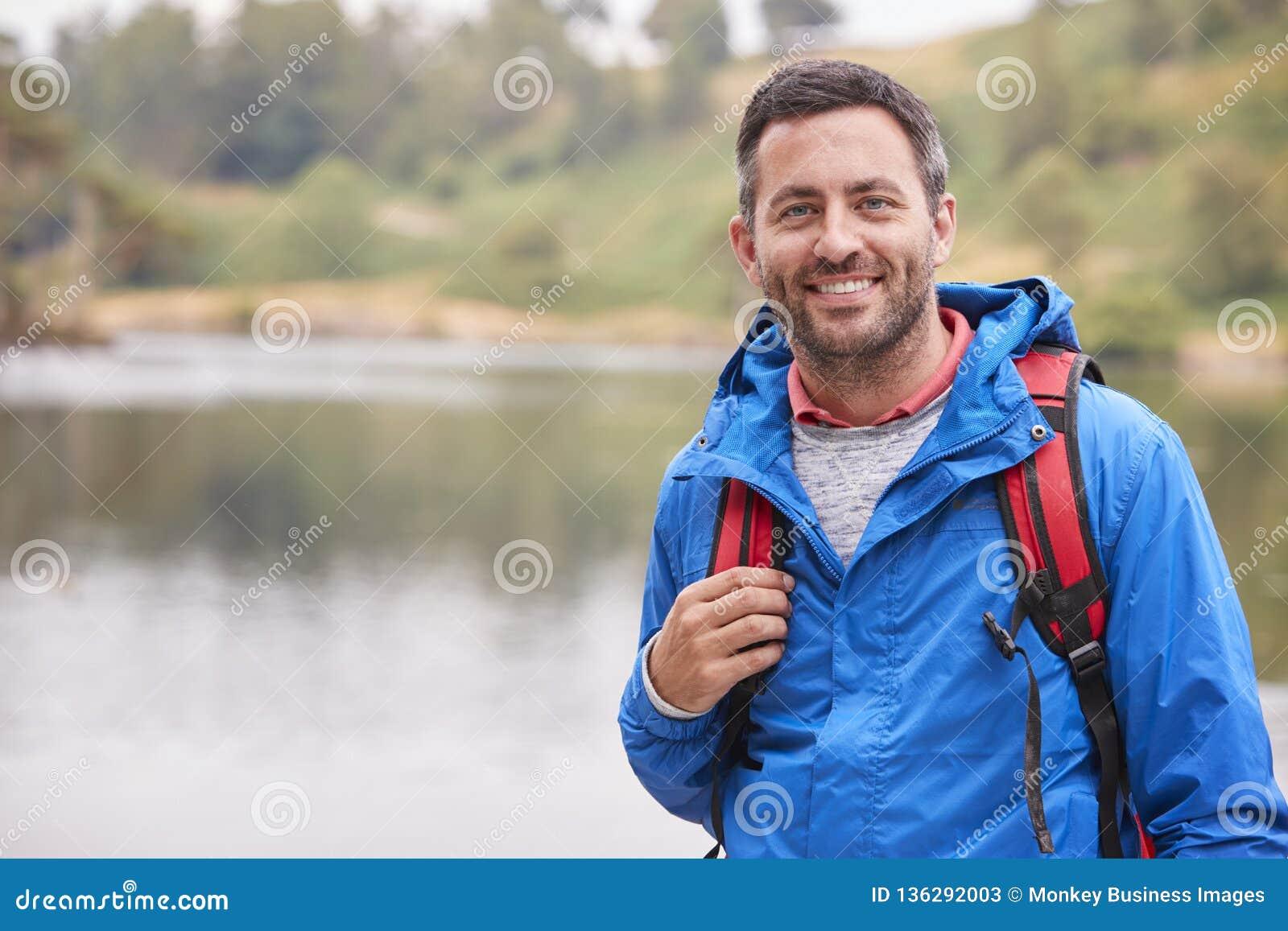 Hombre adulto en una acampada que hace una pausa un lago que sonríe a la cámara, retrato, distrito del lago, Reino Unido