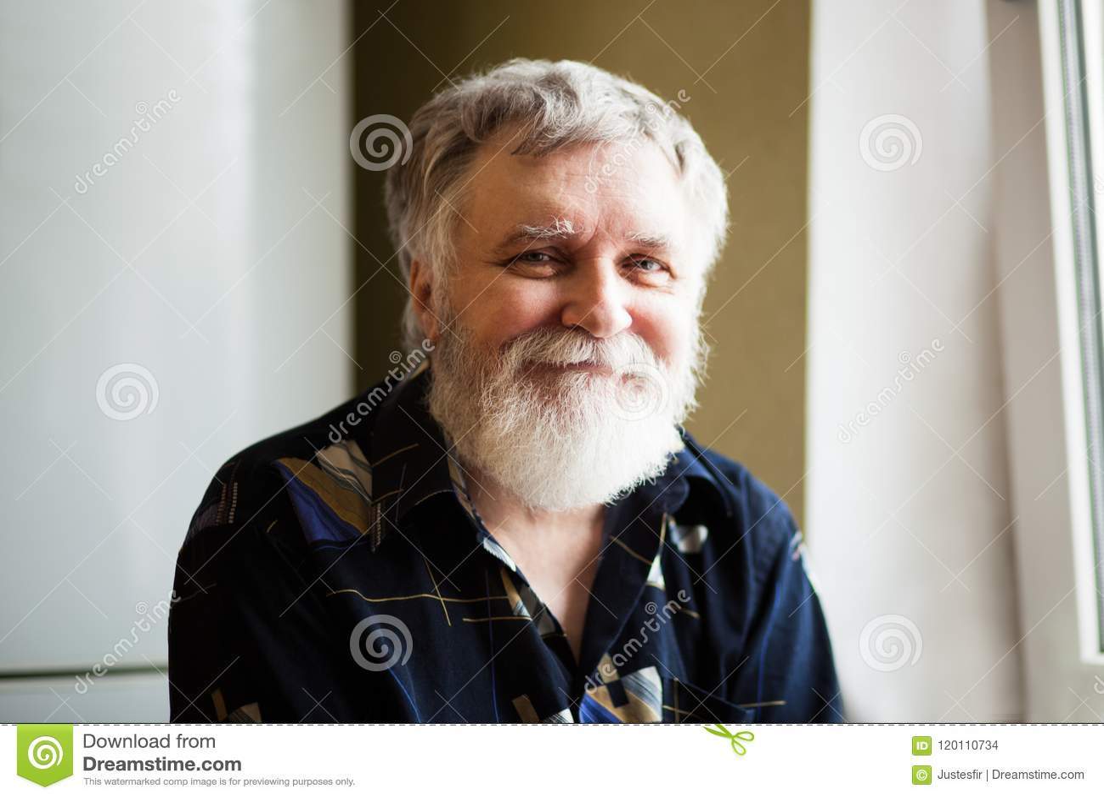 Hombre adulto feliz con el pelo gris que mira en la cámara y la sonrisa