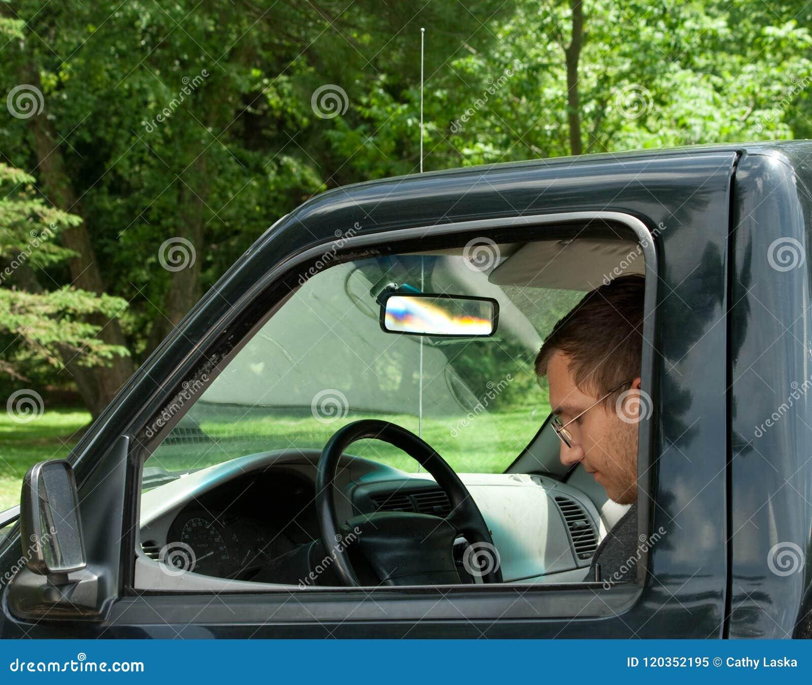 Hombre adulto joven que se sienta en el camión en el parque