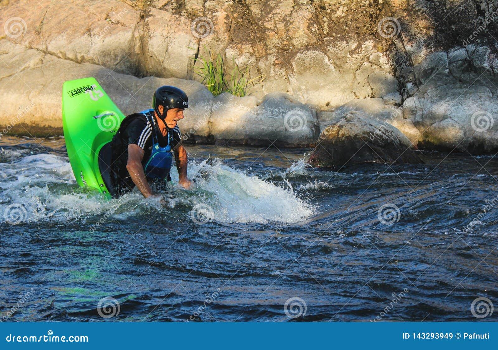 Hombre adulto que bate un kajak en el río