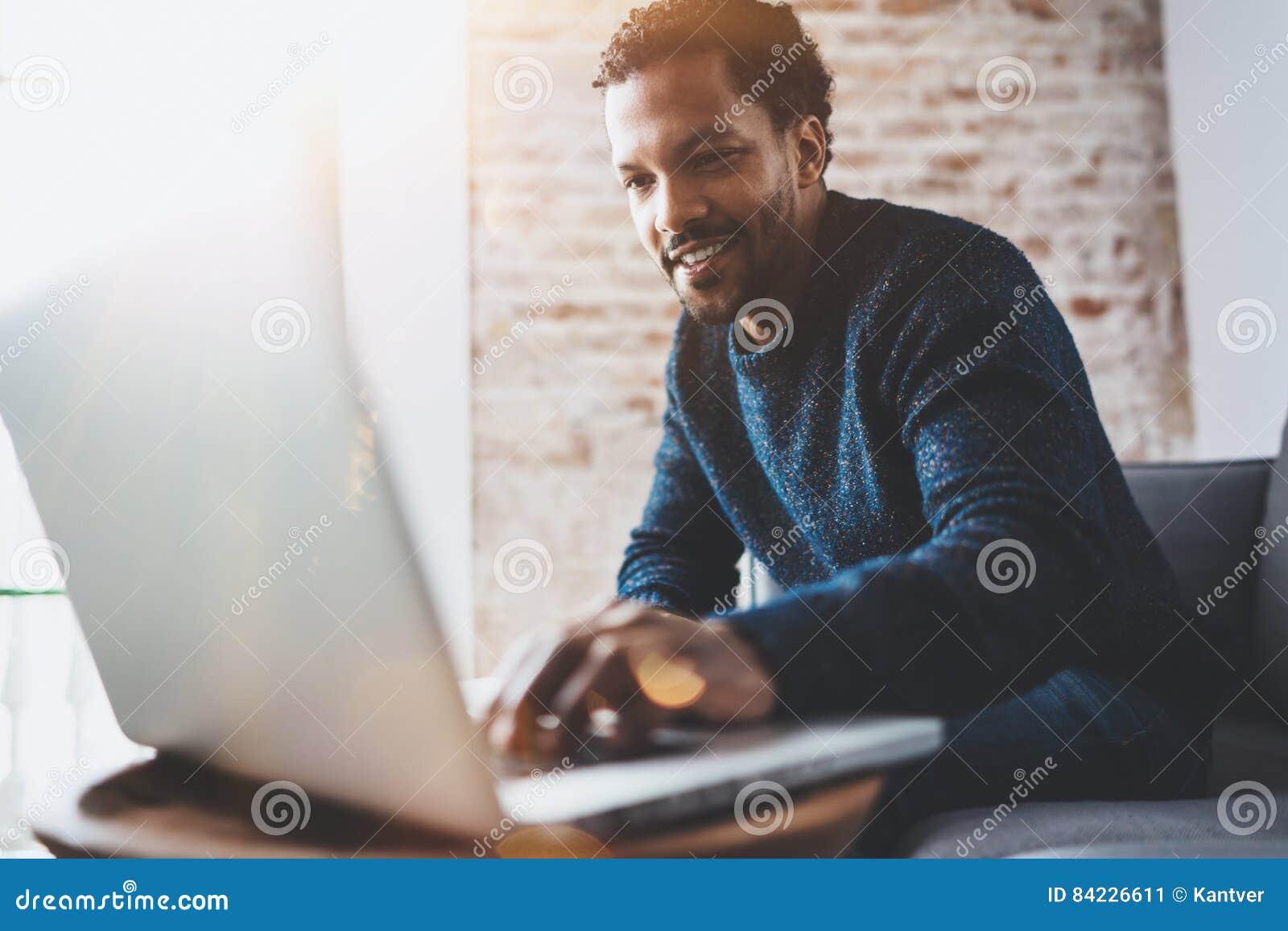 Hombre africano alegre que usa el ordenador y sonriendo mientras que se sienta en el sofá Concepto de hombres de negocios jovenes
