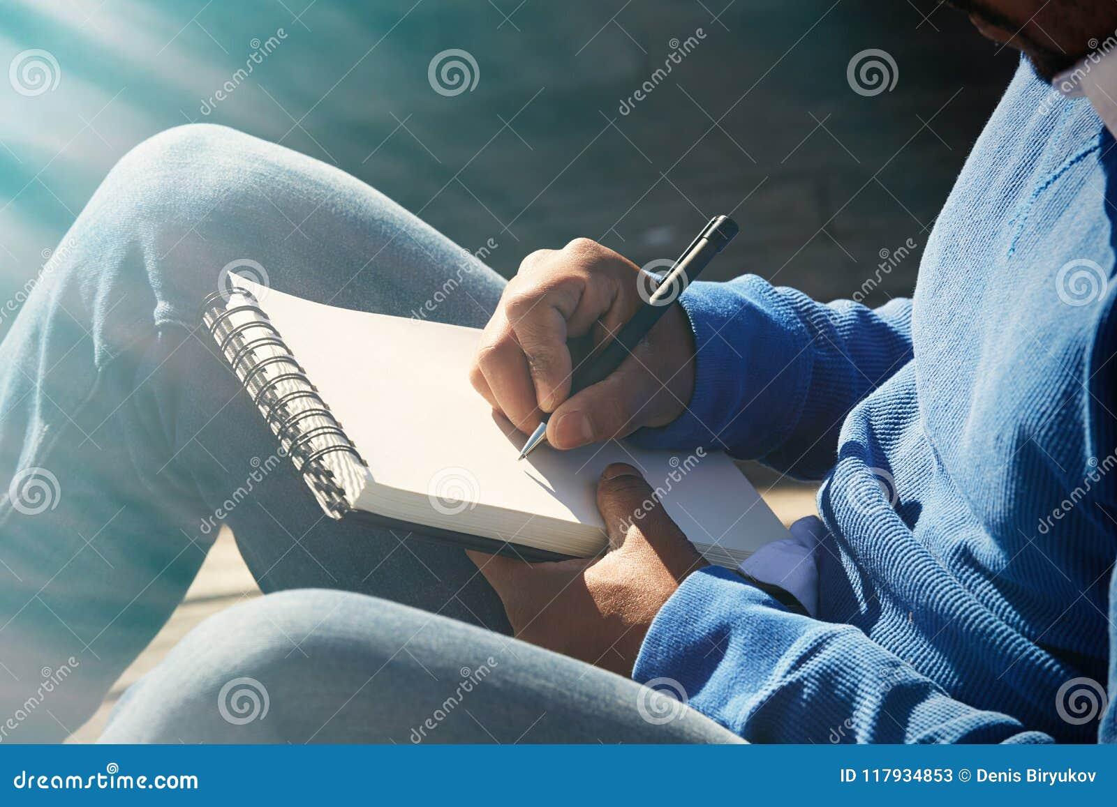Hombre africano americano joven ocasional vestido atractivo que hace notas en cojín del cuaderno Estudiante que se prepara para l