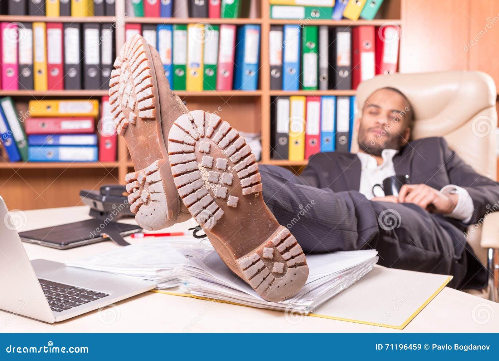 Hombre africano cansado que duerme en la oficina