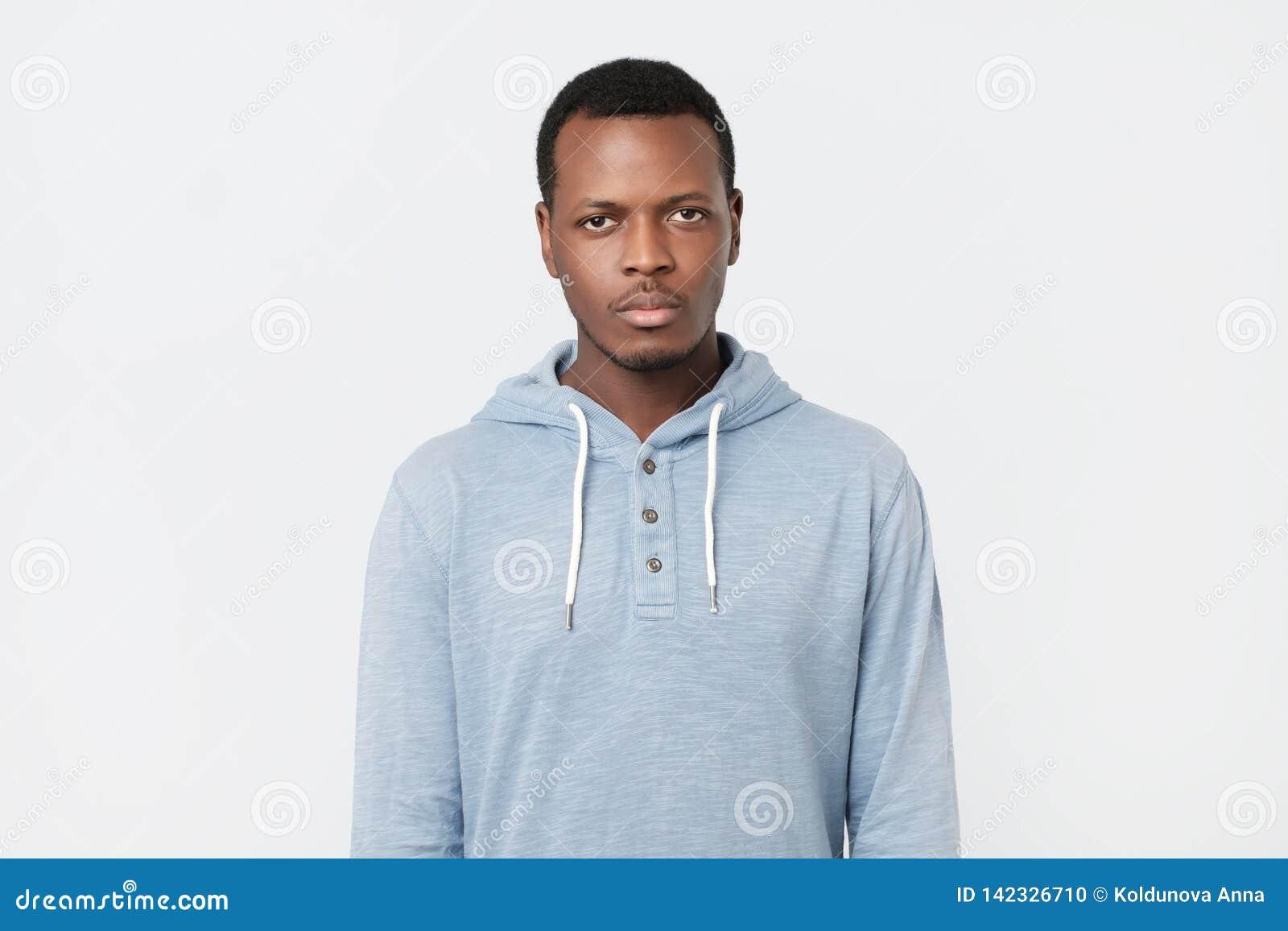 Hombre africano con la expresión seria que mira la cámara mientras que presenta contra la pared blanca del estudio