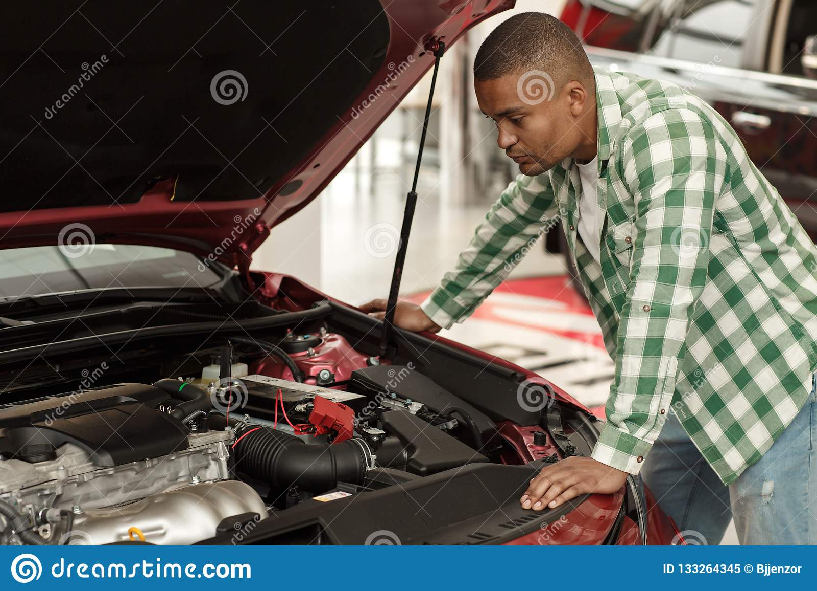 Hombre africano hermoso que elige el nuevo coche en la representación
