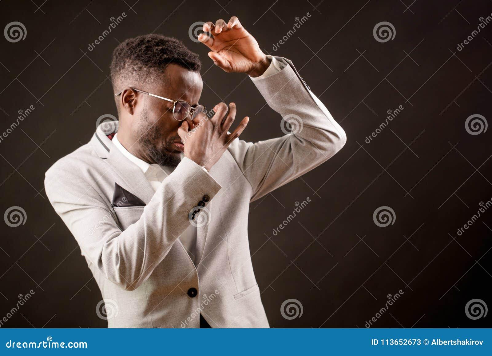 Hombre africano que se cierra la nariz con el finger debido a stentch tremendo