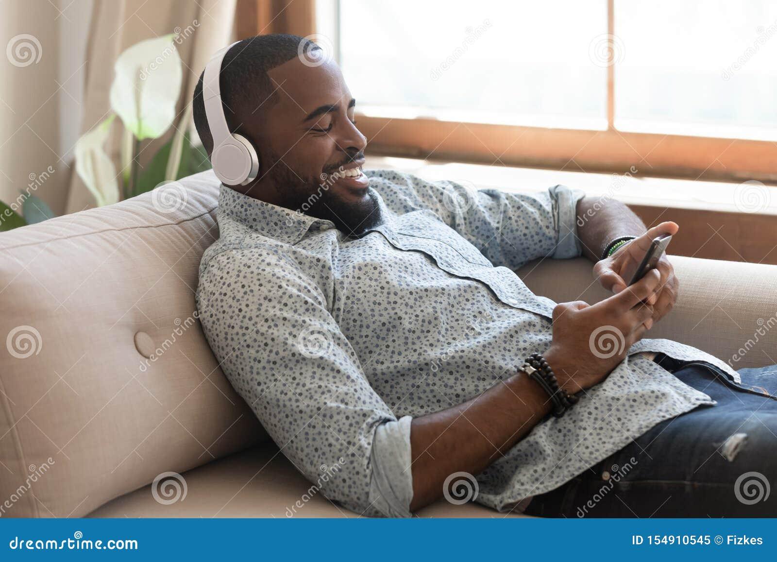 Hombre africano relajado que lleva música que escucha de los auriculares inalámbricos en smartphone