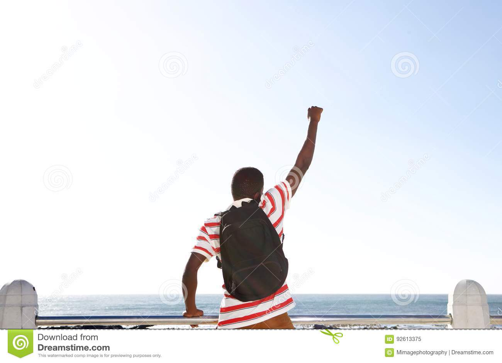 Hombre afroamericano joven emocionado que mira el mar