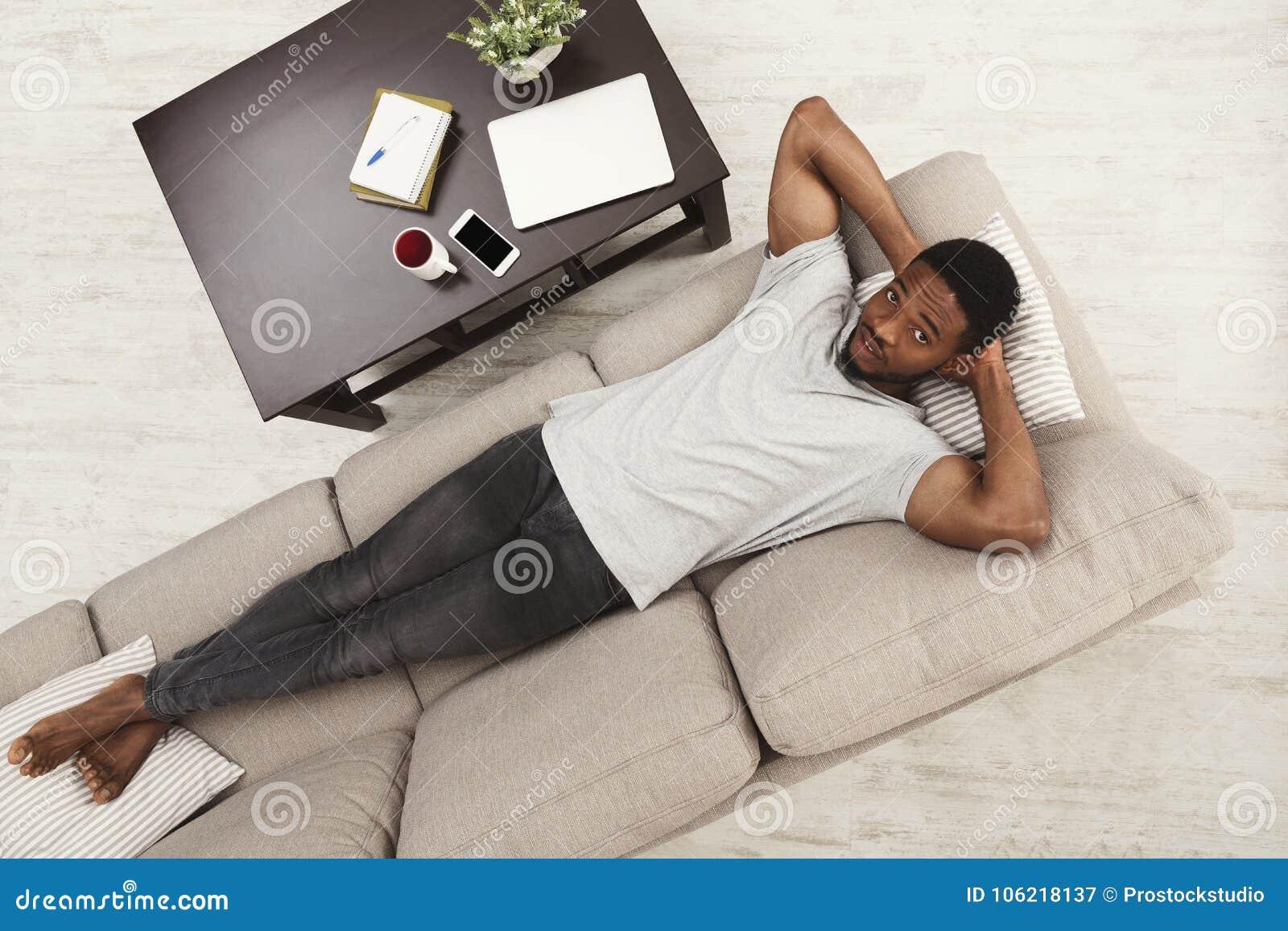 Hombre afroamericano joven hermoso que se relaja en el sofá en casa