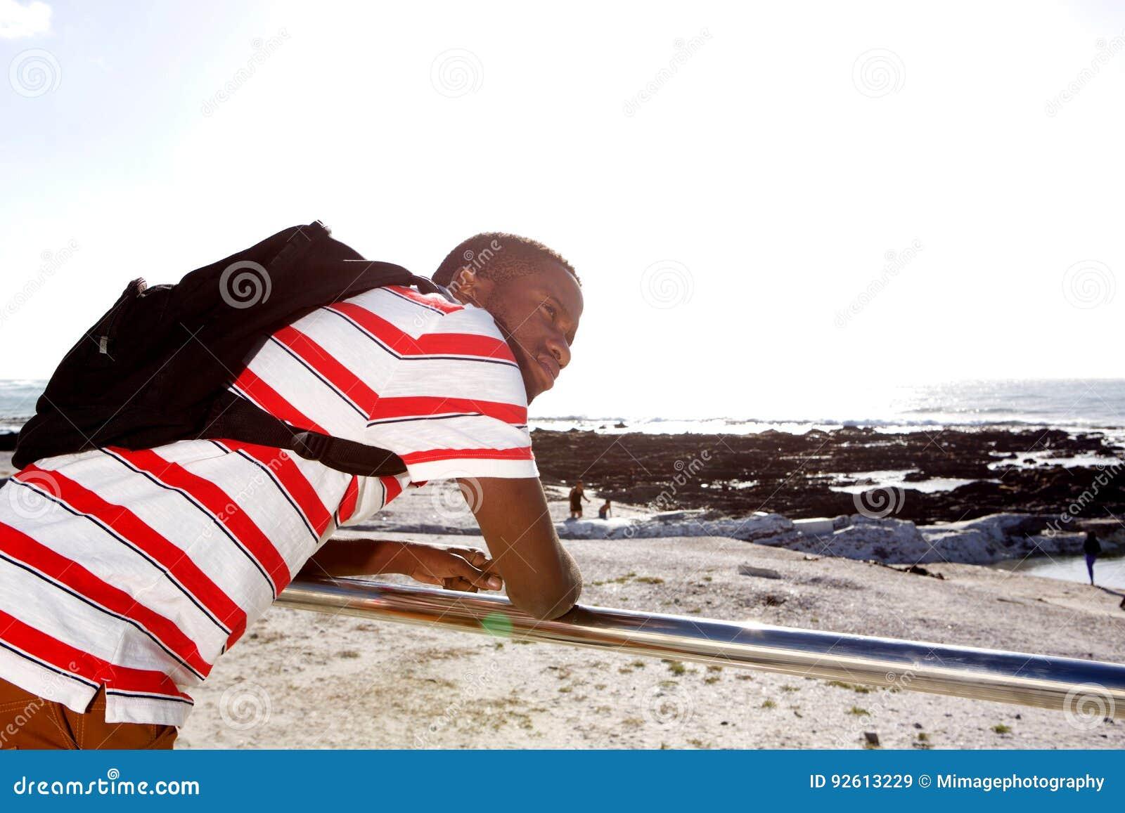 Hombre afroamericano joven que mira la playa