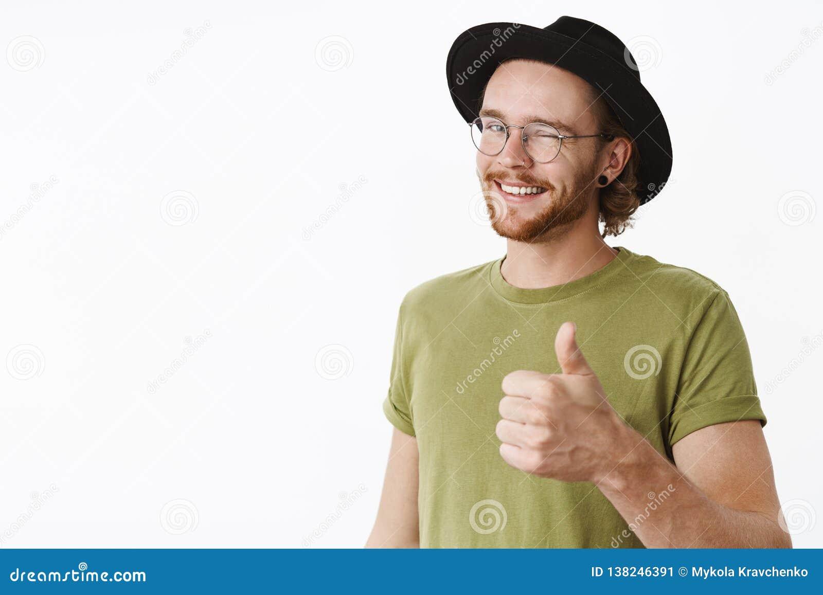 Hombre agradable del trabajo, como él Varón barbudo encantador feliz y amistoso satisfecho en sombrero y vidrios que guiña mostra