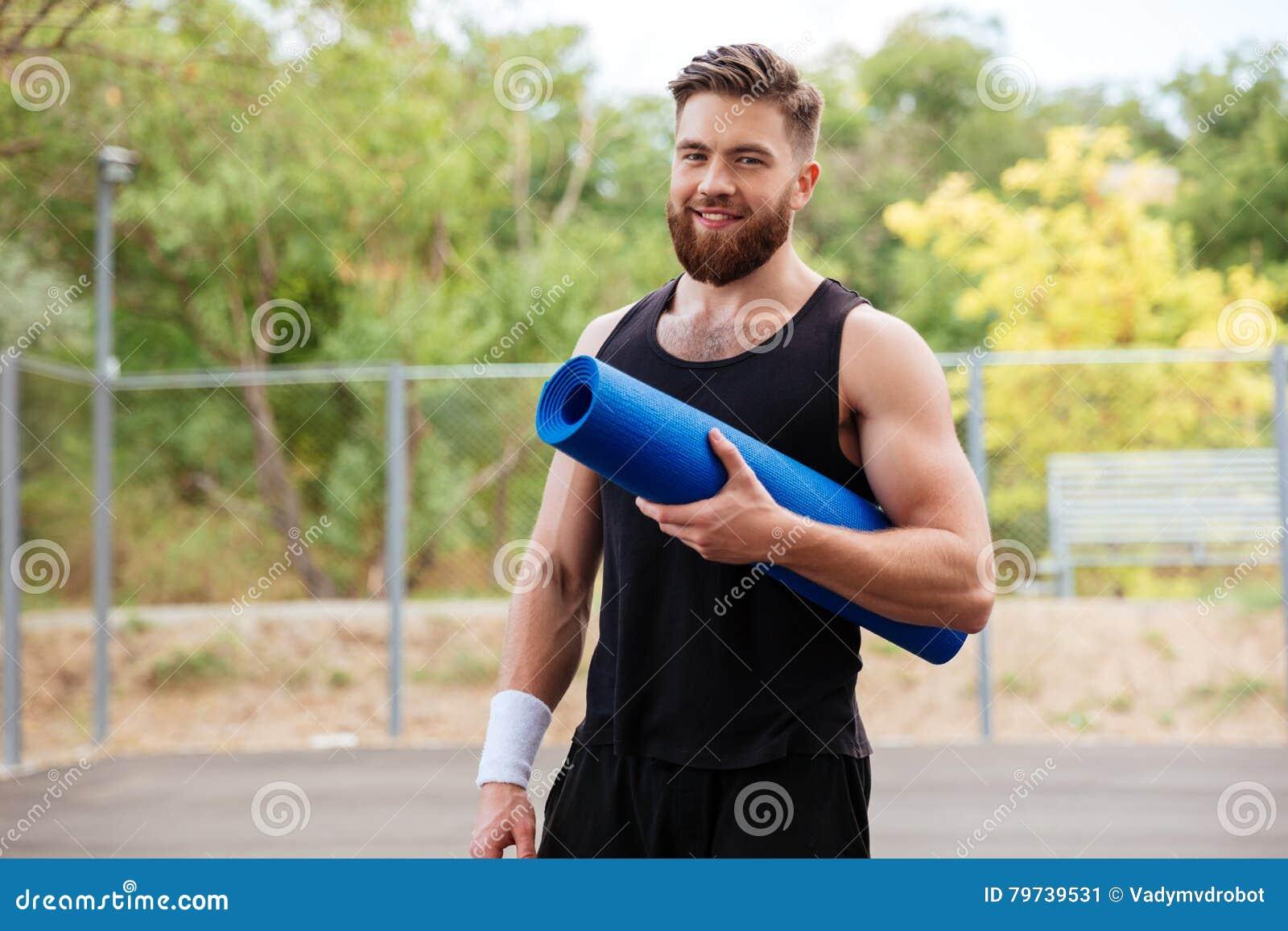 Hombre alegre sonriente de la aptitud con la estera de la yoga que se coloca al aire libre