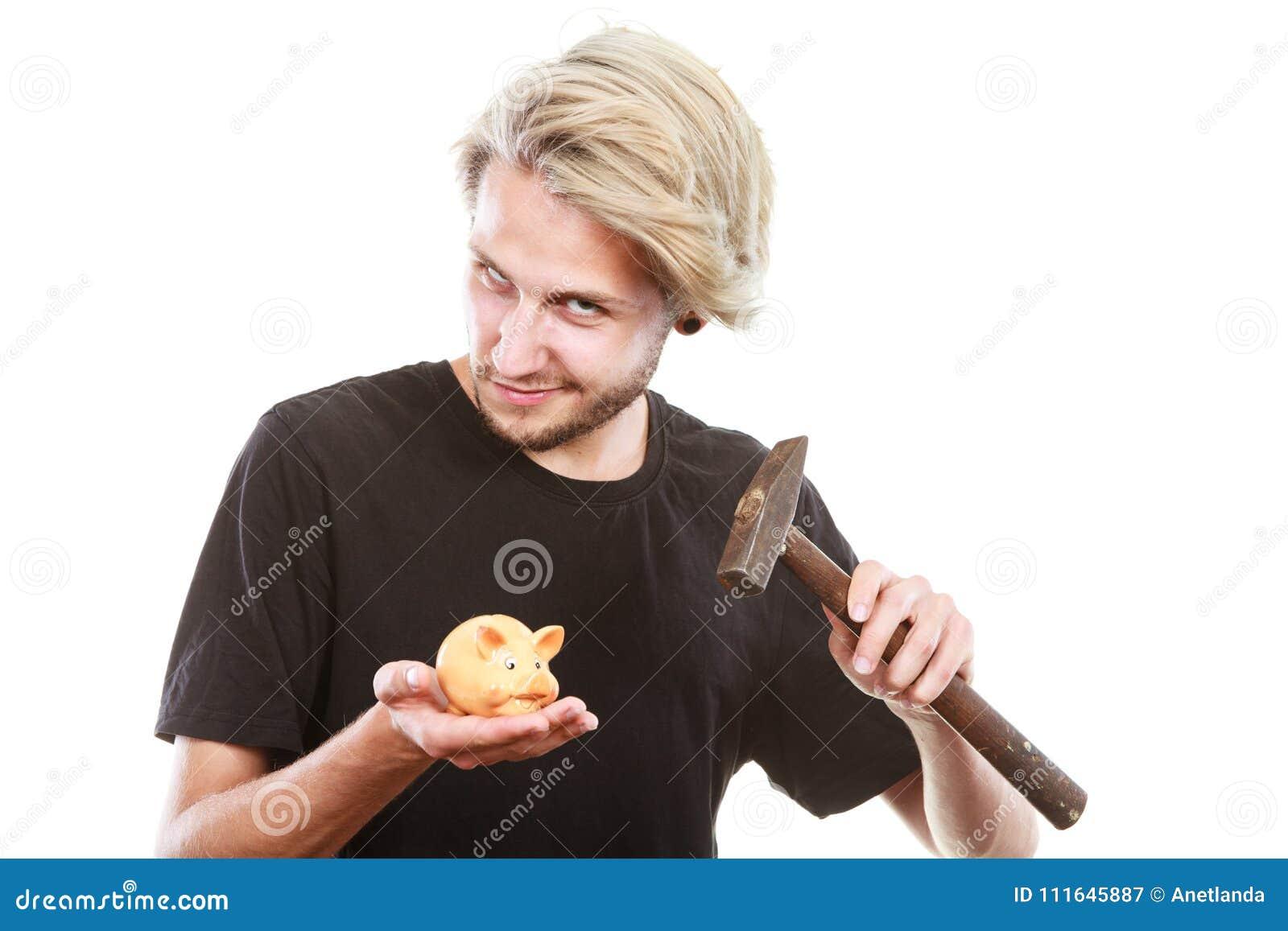 Hombre alrededor para romper la hucha con el martillo