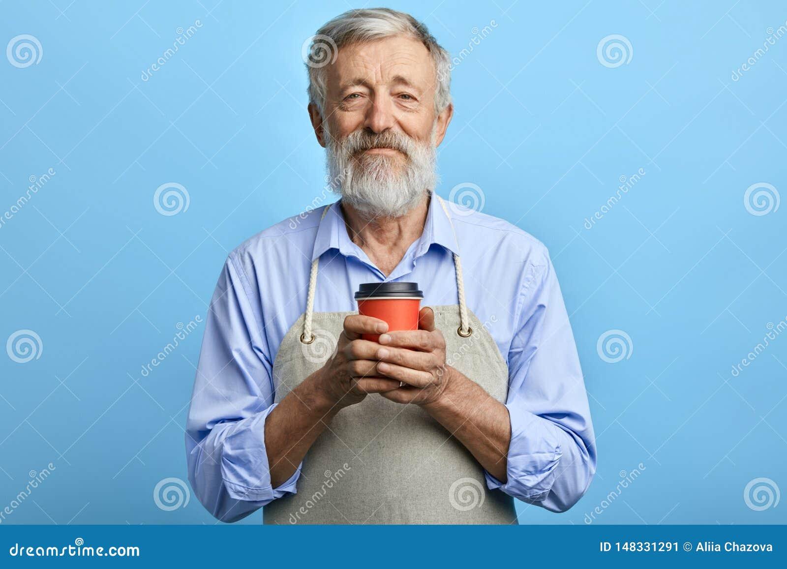Hombre amistoso en el delantal gris que sostiene la taza disponible de bebida caliente