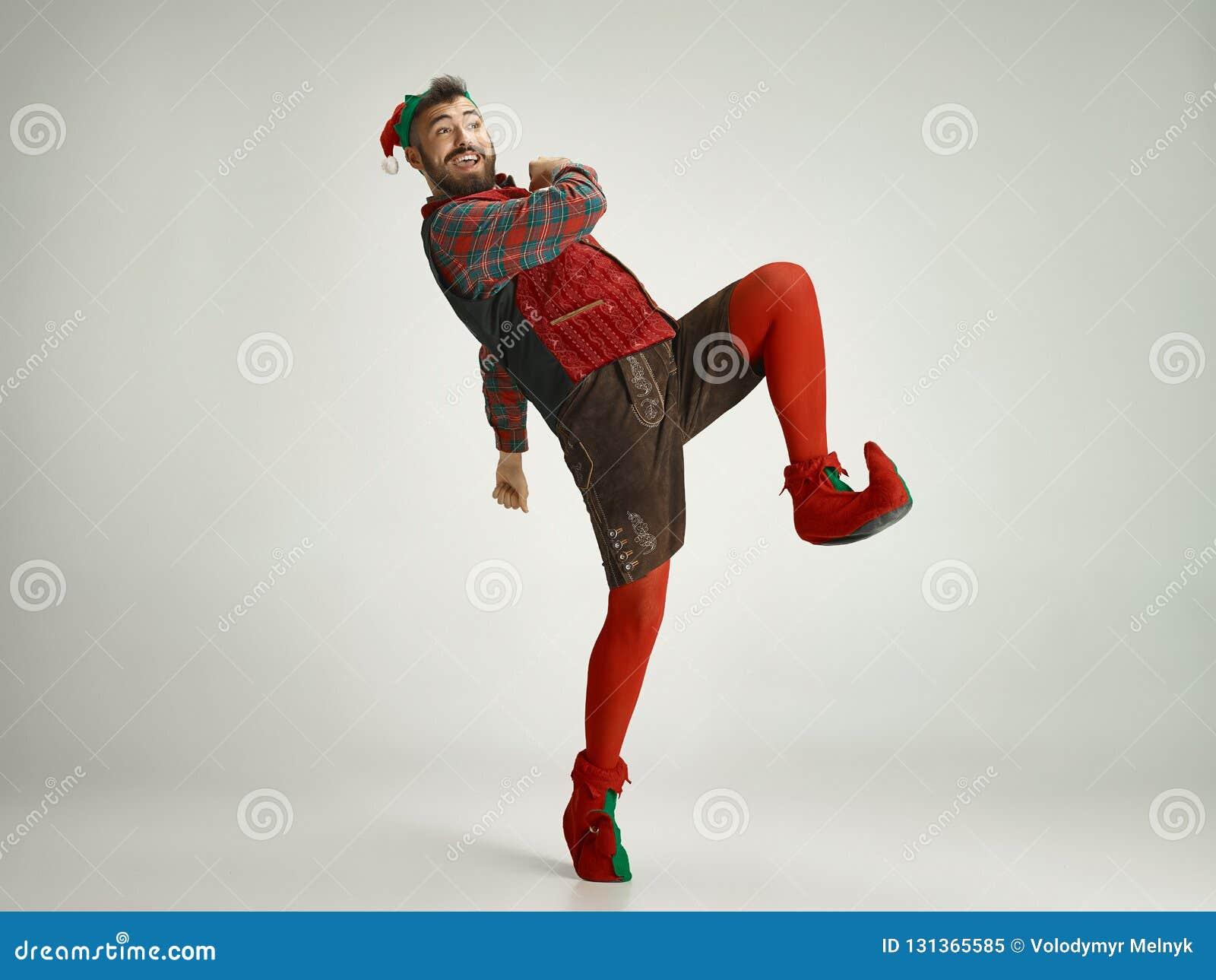 Hombre amistoso vestido como un gnomo divertido que presenta en un fondo gris