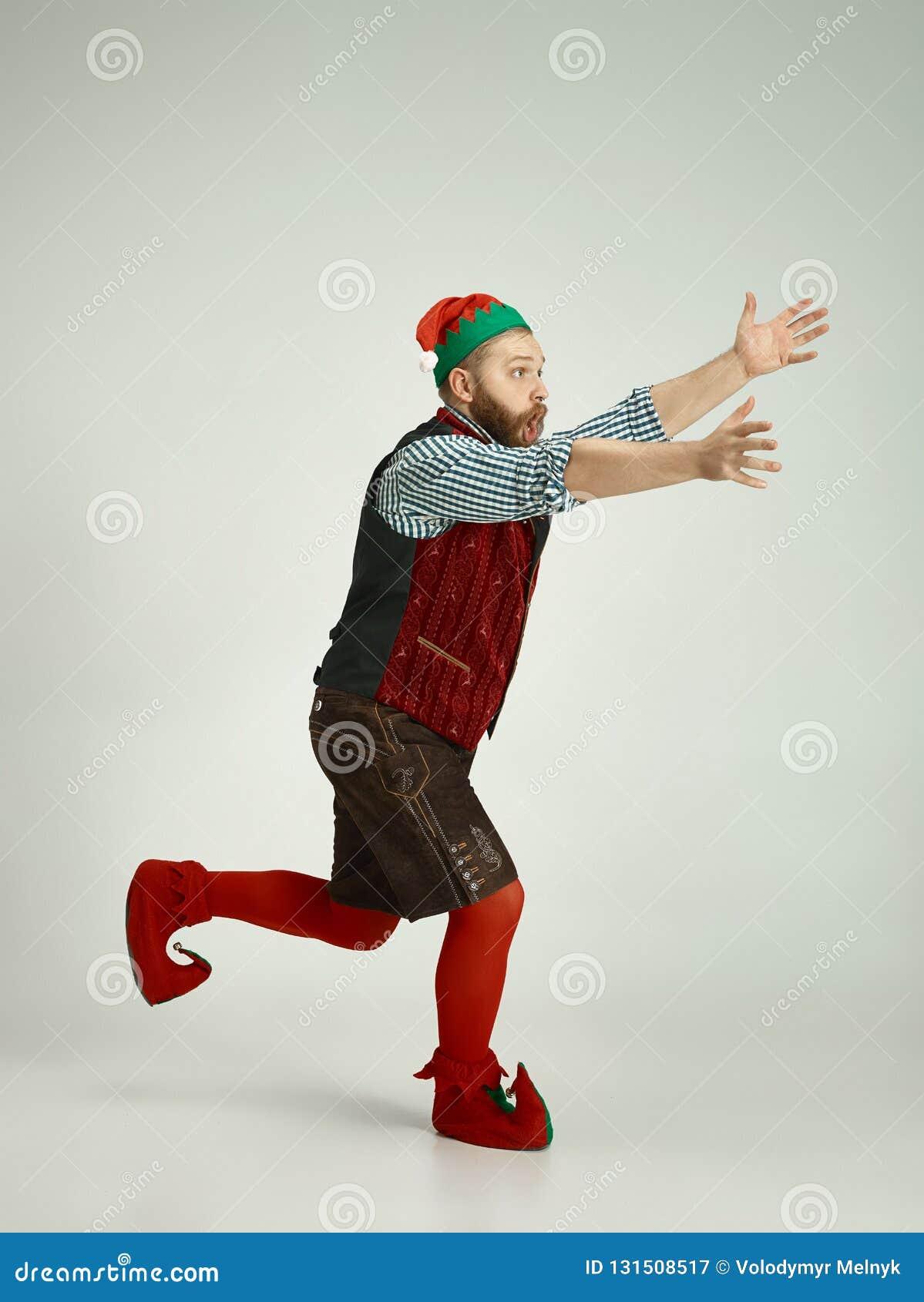 Hombre amistoso vestido como un gnomo divertido que presenta en un fondo gris aislado