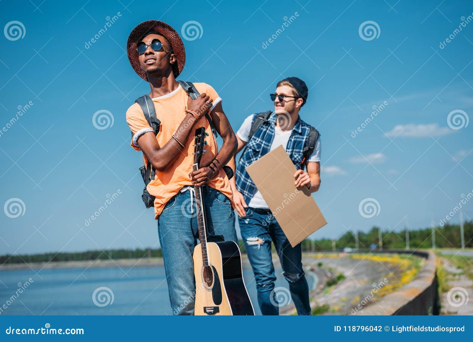 Hombre amrican africano joven con la guitarra que hace autostop