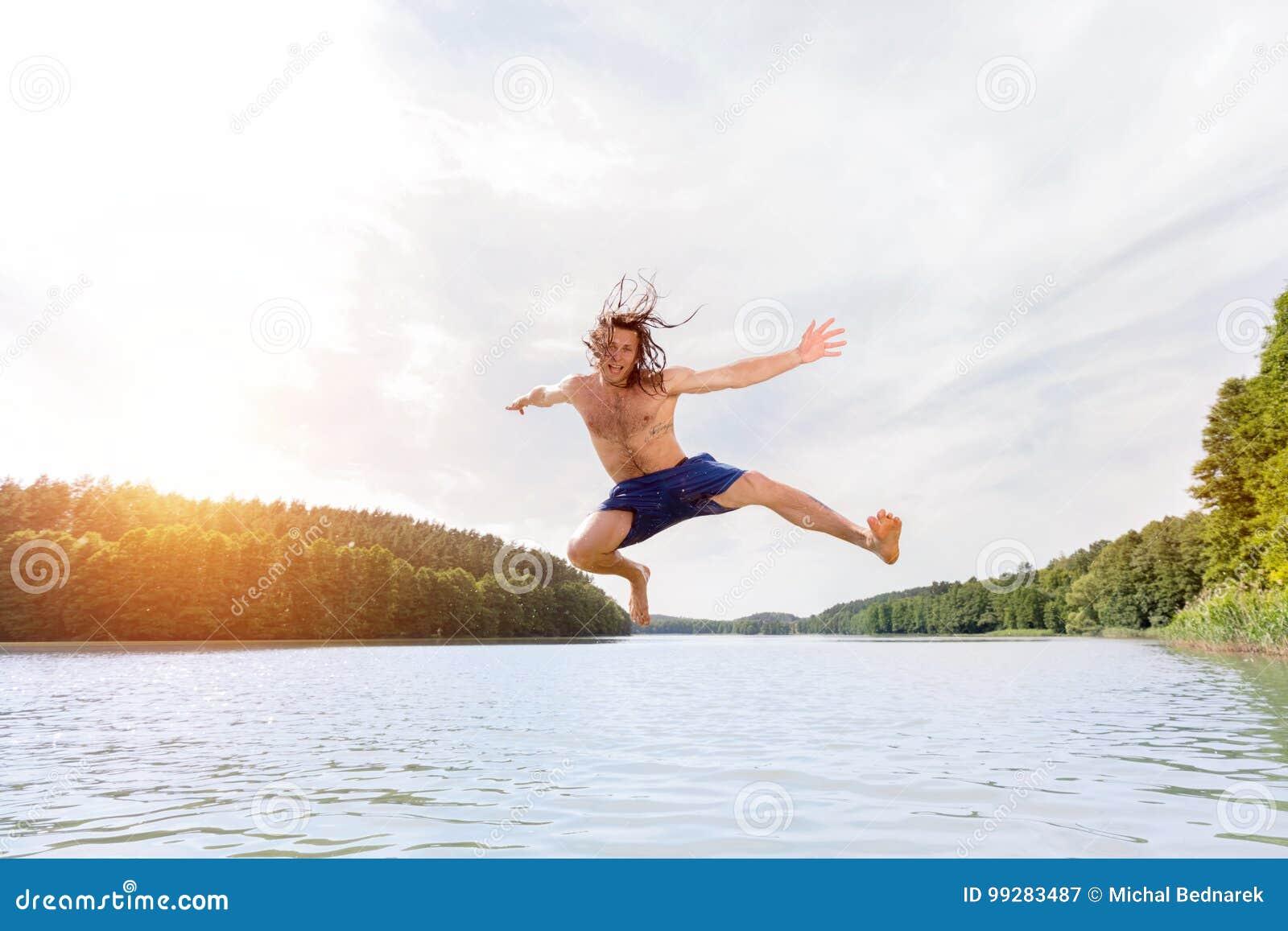 Hombre apto de los jóvenes que hace un salto en un lago