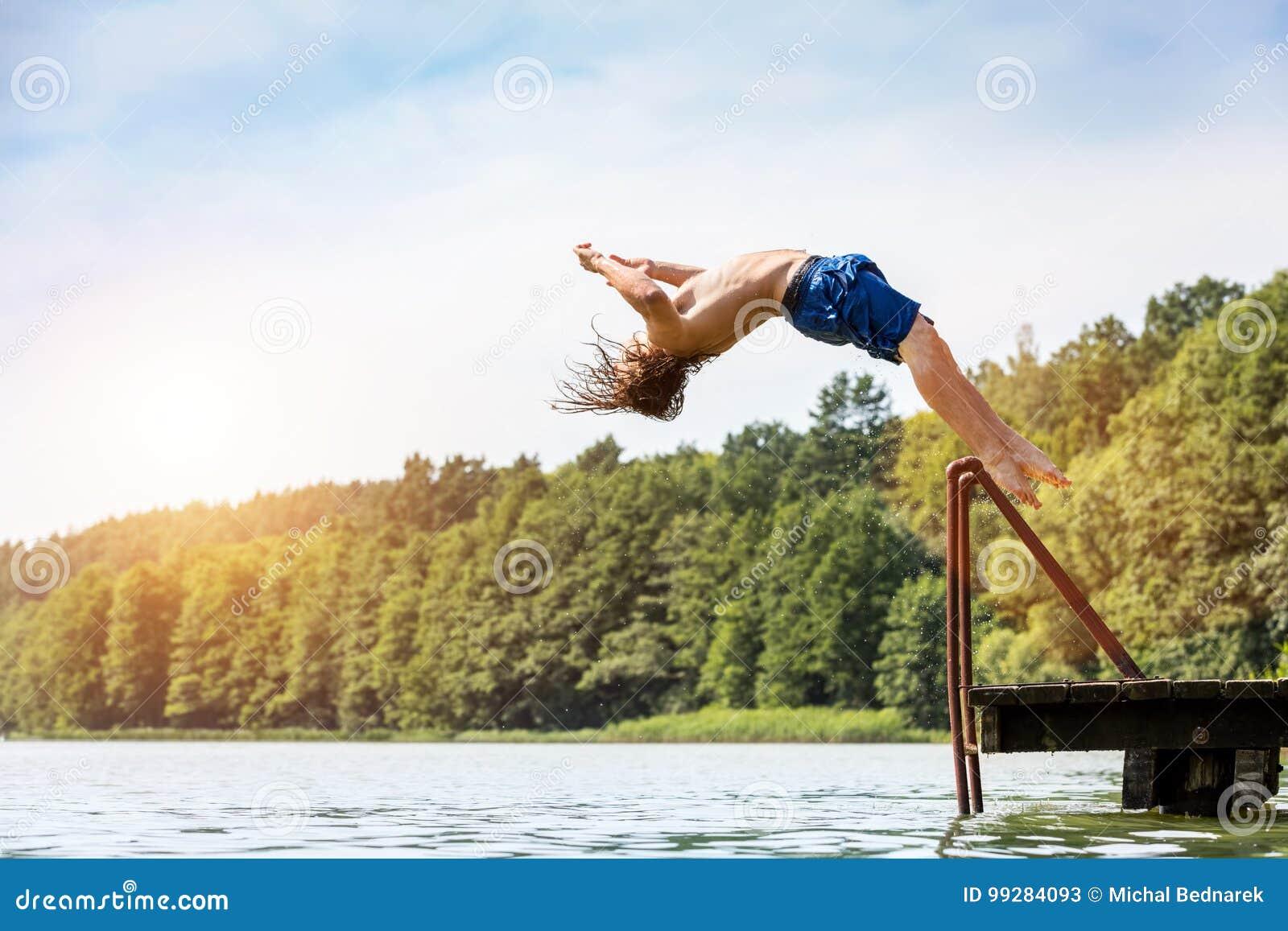 Hombre apto de los jóvenes que salta en un lago