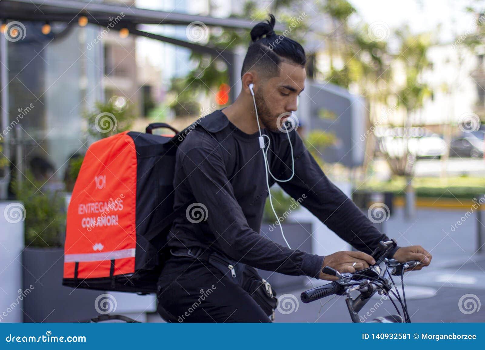 Hombre apuesto en el funcionamiento de la bici para el servicio de entrega de la comida de Rappi