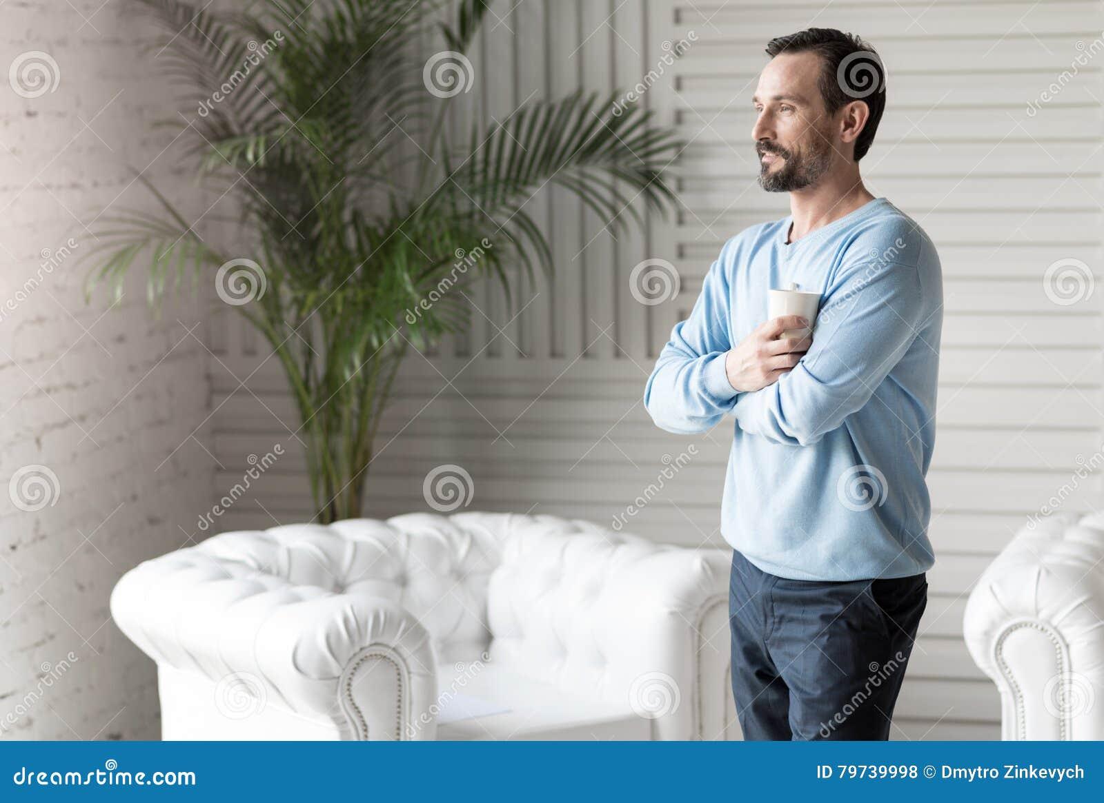 Hombre apuesto encantado que cruza sus brazos