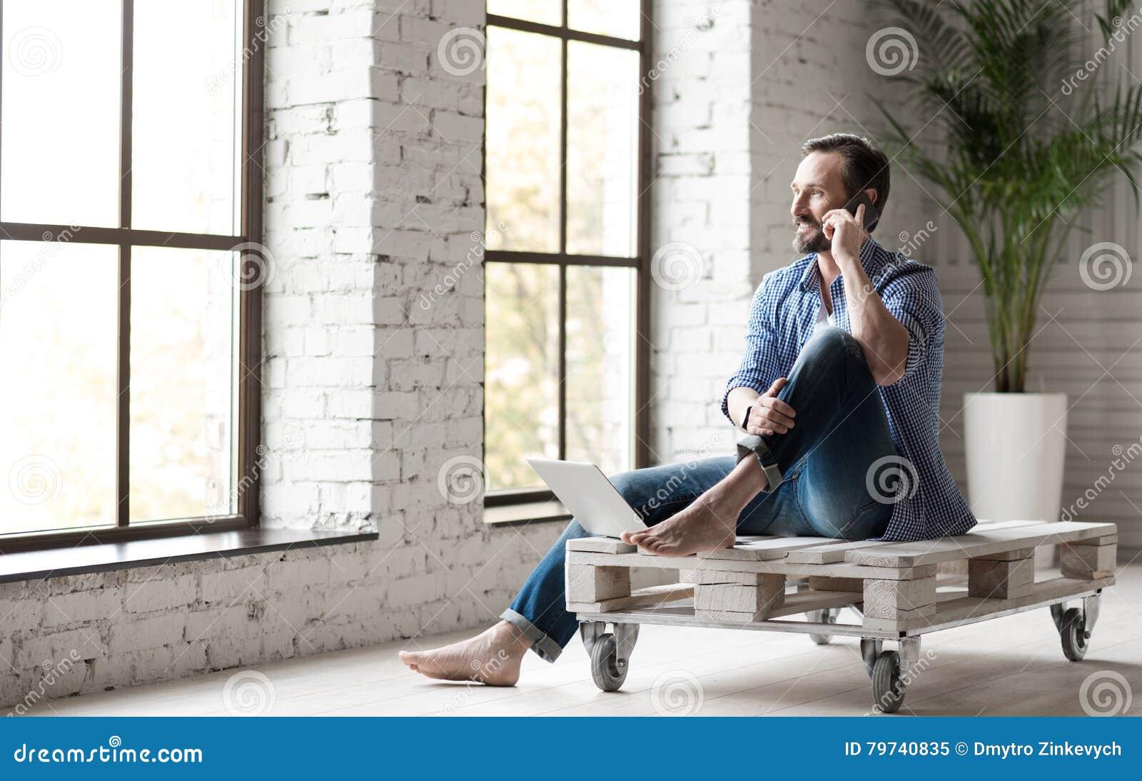 Hombre apuesto positivo que habla en el teléfono