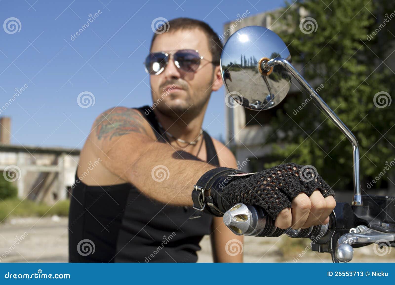 Hombre apuesto que sostiene una maneta de la motocicleta