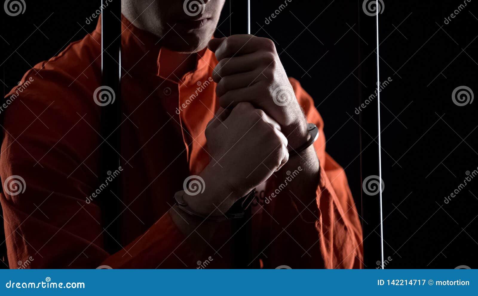 Hombre arrestado en esposas detrás de las barras que sienten enojadas sobre plan fallado del robo