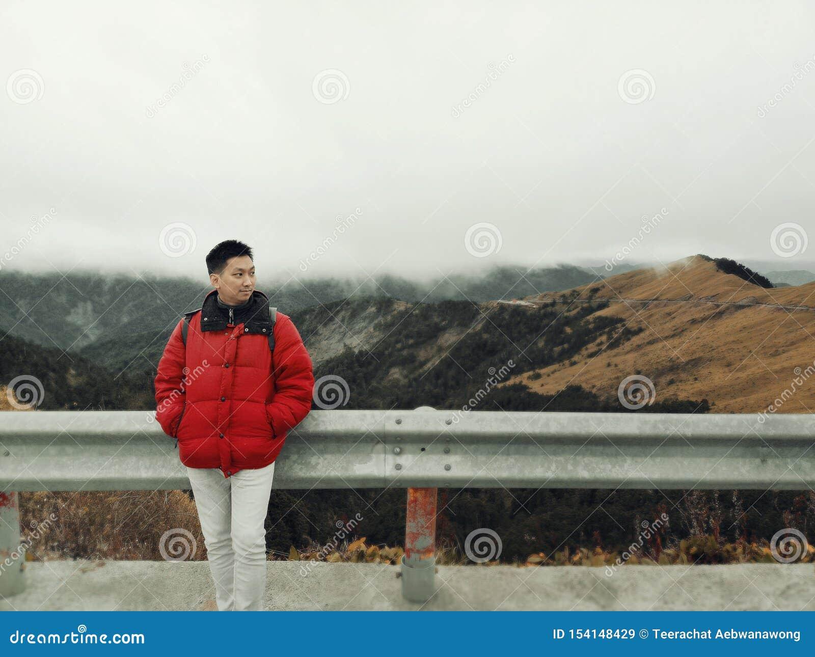 Hombre asiático joven que goza en el viento y la niebla en el top de la montaña con paisaje hermoso en fondo